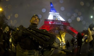 A French soldier in front of the Eiffel Tower, which is illuminated with the colours of the French national flag.