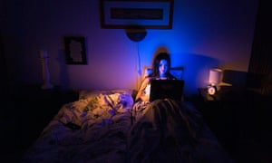 Young woman using a laptop sitting up in bed next to an empty duvet