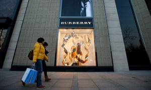 People walk past a Burberry store in Beijing