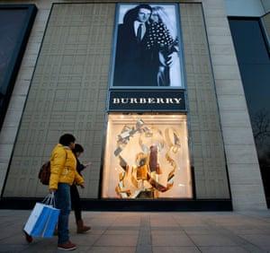 People walk past the window display of a Burberry store in Beijing