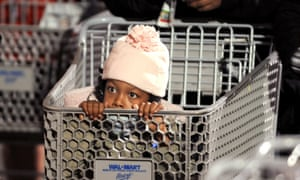 Nevaeh Enoch, 6, peers out from a shopping cart while waiting for a Wal-Mart to open around 5 a.m. Friday, Nov. 28, 2008, in Oakland, California, USA. Hoping for deals on clothes and toys, Enoch and her mom joined the line of several hundred people at 2:45 a.m. (AP Photo/Noah Berger)