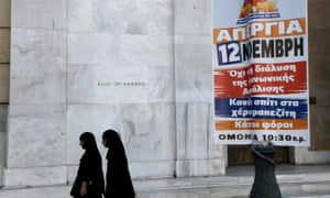 Two nuns walk past a poster calling for a nationwide 24-hour strike, outside the Bank of Greece, in central Athens.