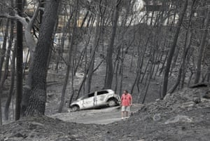A man stands amongst the charred trees and a burned-out car near the village of Neos Voutzas