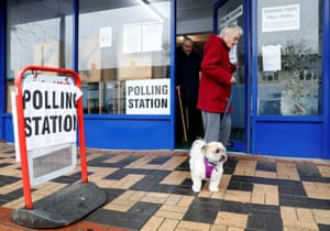 A woman leaves with her dog after casting her vote at a laundrette, set up as a polling station in Oxford