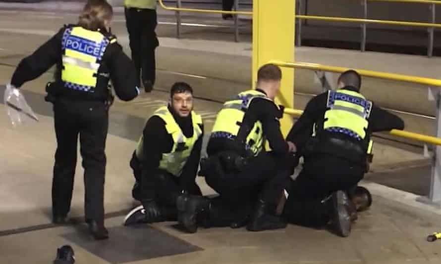 Police restraining a man after three people were stabbed at Victoria Station in Manchester last New Year's Eve