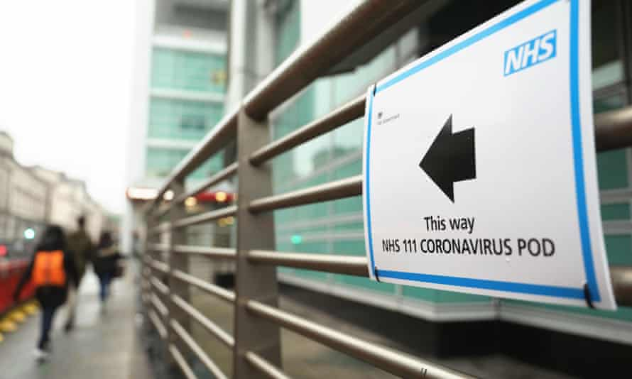 A sign directs directs patients to an NHS 111 Coronavirus Pod testing area at University College Hospital in London