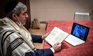 French Rabbi Philippe Haddad speaks to congregation members during the Shabbat service by visioconference at the Copernic Synagogue in Paris on 28 March 2020.
