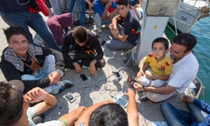 Syrian refugees charge their phones on the Greek island of Lesbos.