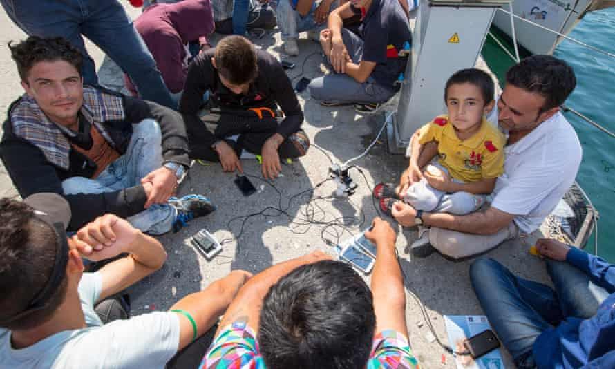Refugees sitting by the shore charging their mobile phones.