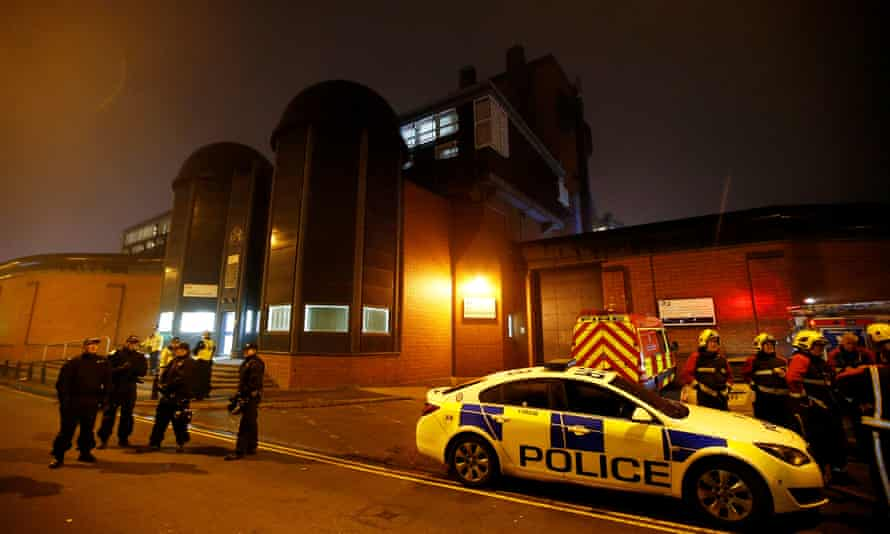 Police officers and firefighters stand outside Winson Green prison, run by security firm G4S, after a serious disturbance in 2016.