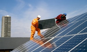 Engineers fitting solar panels to a roof
