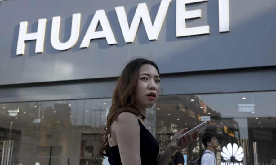 A woman uses a smartphone outside a Huawei store in Beijing
