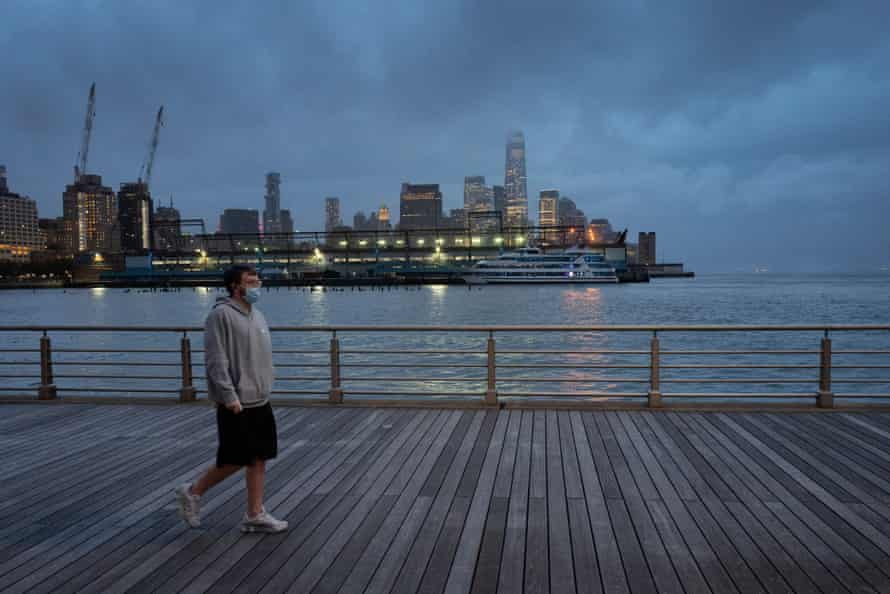 A young man wears a face mask as he walks on Pier 45 in Hudson River Park in New York in April.