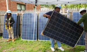Richard Cochran (center) and Rico Jackson (right), workers with Grid Alternatives, position a solar panel at a Northeast D.C. residence.
