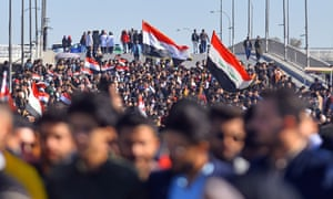 Iraqi students hold national flags during an anti-government demonstration in the central Iraqi city of Najaf.