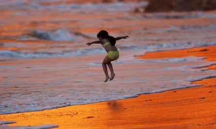A child plays in surf reddened by the reflection of heavy smoke in Montecito, just south of Santa Barbara.