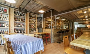 Corkage in Bath, with a tablecloth on one table, high stools at the bar and wine bottles on shelves in the wall