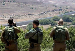 Israeli soldiers look on as Syrian refugees march towards the Israeli security fence