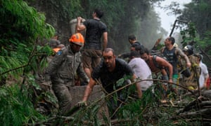Firefighters and others take part in a rescue operation after heavy rains in Rio de Janeiro.