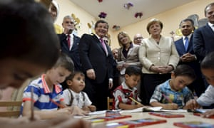 Merkel and Davutoğlu watch a group of children writing