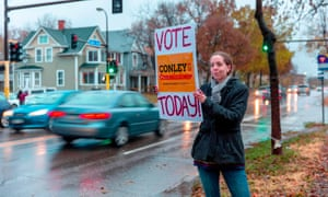 Campaigners hold signs outside a polling station Minneapolis, Minnesota on 6 November.