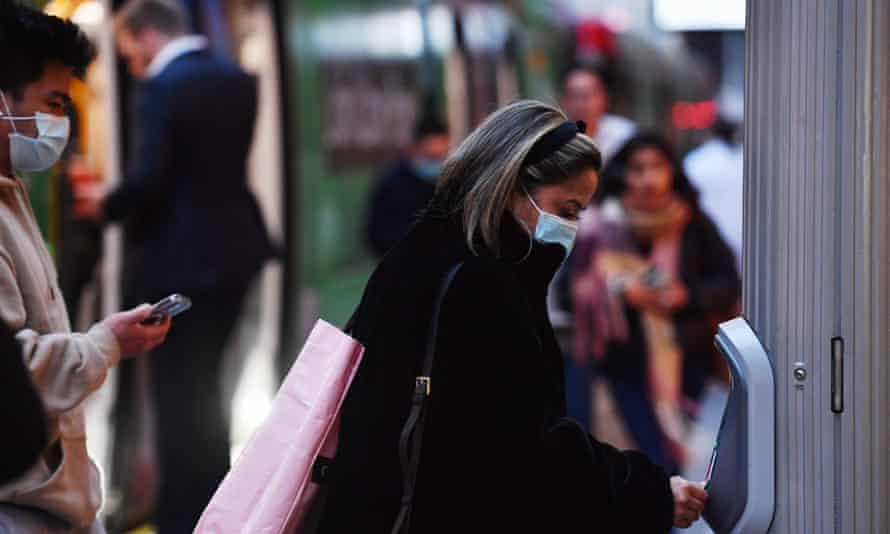 Commuters hop off a tram wearing face masks in Sydney