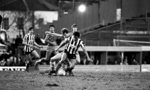 Grimsby and Chelsea players battle for the ball on a muddy pitch, with empty stands behind them.