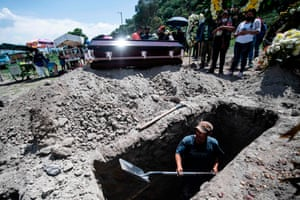 San Miguel, Mexico: A man digs a grave during a funeral at the Xico cemetery