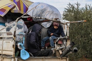 Children ride in the back of a truck near the Turkish border in Jindayris, Syria