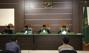 Two men accused of having gay sex sit during their trial at Sharia court in Banda Aceh, Indonesia.