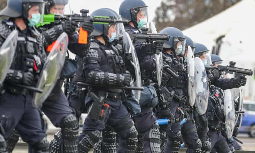 Riot police on guard at the bottom of Westgate Bridge as thousands march through Melbourne