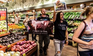After holding a 'flash speak out' in the meat aisle of Ralphs Supermarket on North La Brea Avenue in West Hollywood, Direct Action Everywhere (DxE) protestors leave the store still chanting and holding signs.