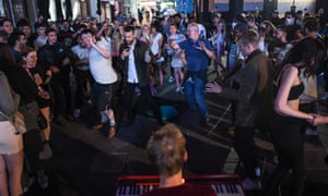 People dance to the music of a busker in Leicester Square