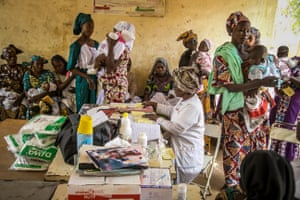 Women wait with their children as they attend a vaccination session at the Baraouéli health centre in Baraouéli, in the Ségou region of Mali