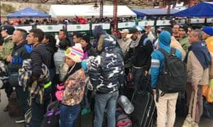 Crowds of Venezuelan migrants wait to cross into Ecuador on the Rumichaca bridge.