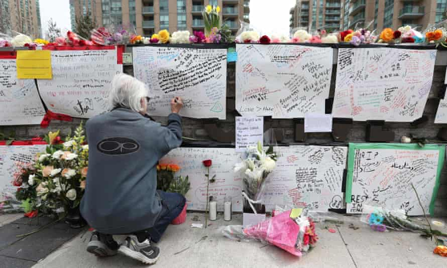 A man leaves a note at a makeshift memorial for the victims of the van attack in Toronto on 24 April 2018.