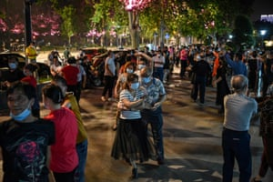Couples wearing face masks dance in a park next to the Yangtze River in Wuhan on 12 May