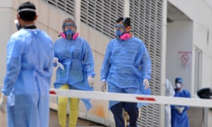 Relatives of deceased patients wearing protective outfits arrive for their remains at Los Ceibos hospital in Guayaquil, Ecuador on 8 April 2020, amid the coronavirus outbreak.