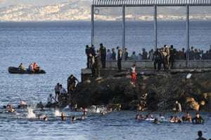 Spanish police watch as people swim to reach the country from Morocco.