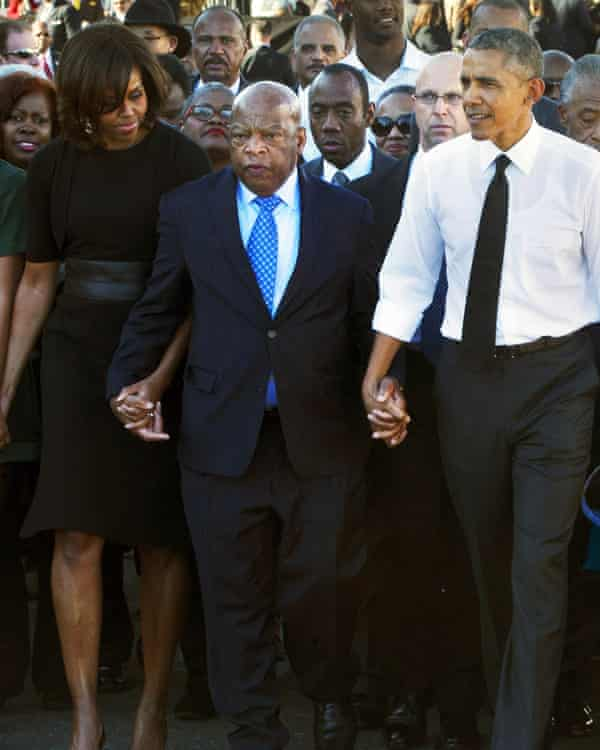 """President Barack Obama and his wife Michelle hold hands with Rep. John Lewis, while marching to mark the 50th anniversary of """"the Bloody Sunday events in 1965."""