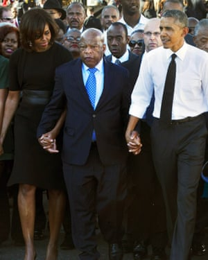 "President Barack Obama and his wife Michelle hold hands with Rep. John Lewis, while marching to mark the 50th anniversary of ""the Bloody Sunday events in 1965."