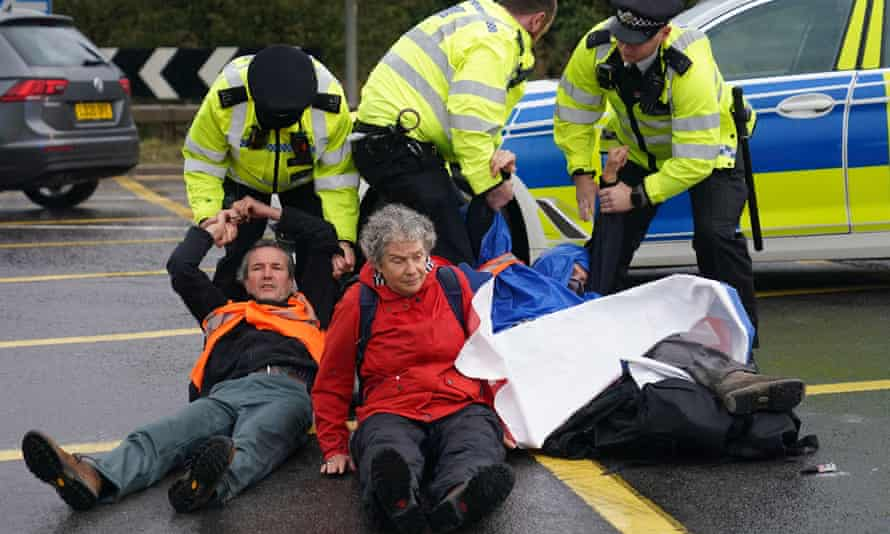 Police officers detain protesters blocking the M25 near Heathrow on Monday.