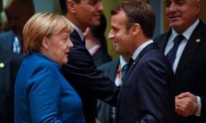 Merkel and Macron greet each other at an EU summit