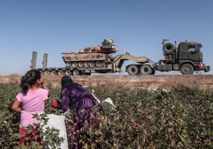 Seasonal workers cut cotton while Turkish military vehicles pass on their way to northern Syria for the military offensive targeting Kurdish forces.
