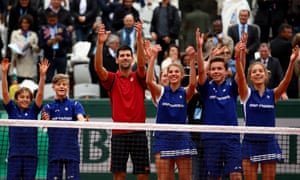 Novak Djokovic celebrates with ball boys and girls after beating Dominic Thiem in their French Open semi-final at Roland Garros on Friday.