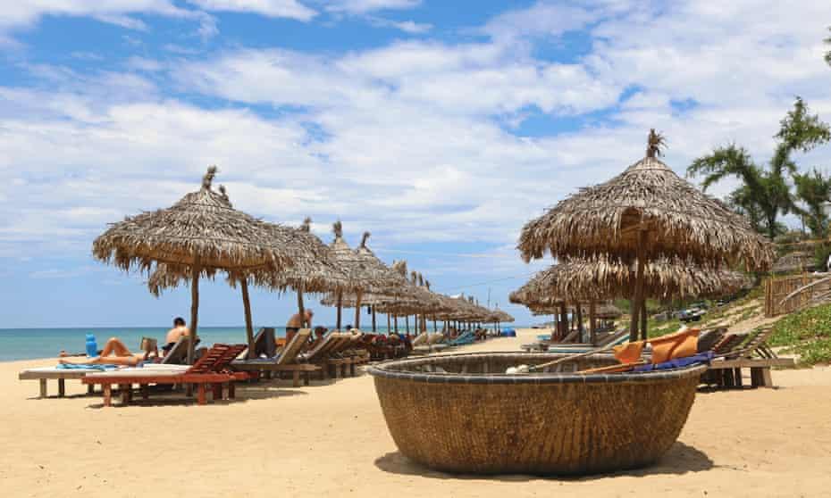 Sun loungers, bamboo shades and coracles on An Bang beach, Hoi An