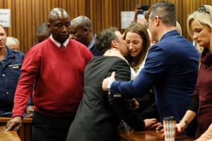 Oscar Pistorius holds his sister Aimee Pistorius as he leaves the High Court in Pretoria.