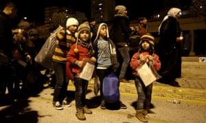 Refugee children disembark from a passenger ferry at Piraeus Port in Greece.