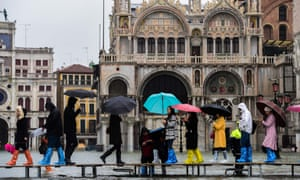Visitors cross the flooded St Mark's Square in Venice on a temporary footbridge during a high tide.