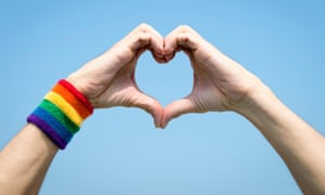 Gay athlete making hand heart with gay pride rainbow colors wristband against blue sky